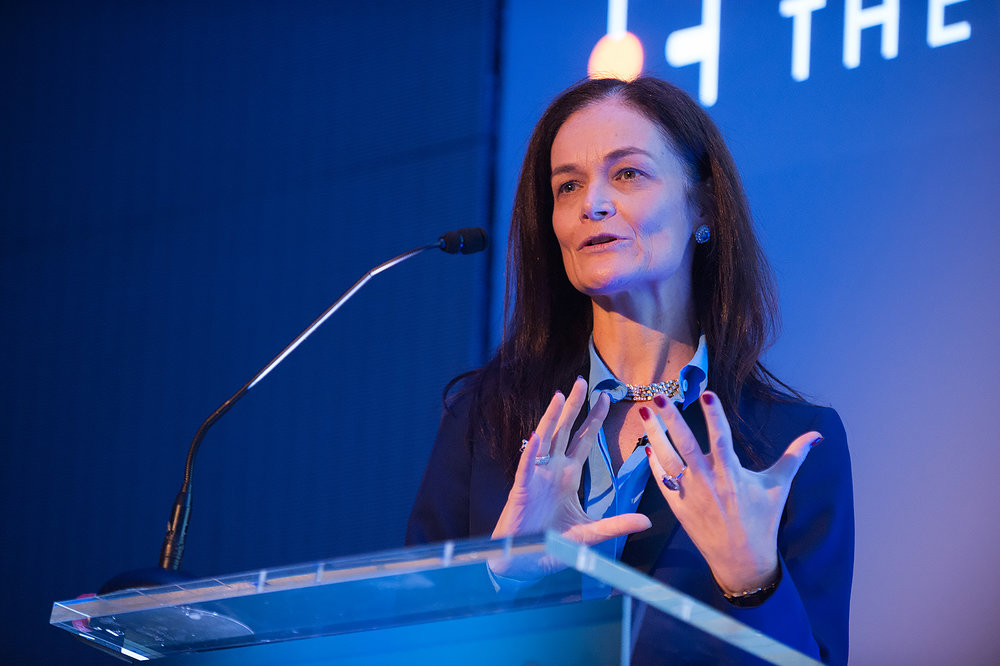 A woman speaking at a  podium at a Conference Event  in London