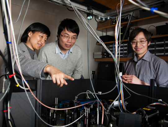 Taking the neuronal skeleton by STORM Xiaowei Zhuang, Ke Xu, and Guisheng Zhong (left to right) gathered around the STORM imaging apparatus used to discover the periodic actin-spectrin structure in axons. Xu and Zhong are co-first authors on the study published in Science. Courtesy of MCB Graphics.