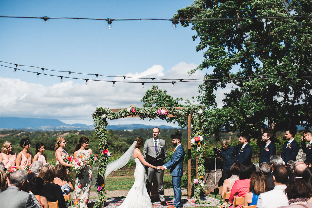 Lauren and Ali exchanging vows amid the beautiful backdrop at Arista Winery. Photo by  Studio Castillero .