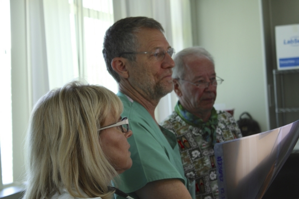 L to R: Dr. Kay Henderson, Dr. Rick Henderson, and Dr. Robert Wells, MD examine x-rays at Majuro Hospital. PC: Brian Hoffman.