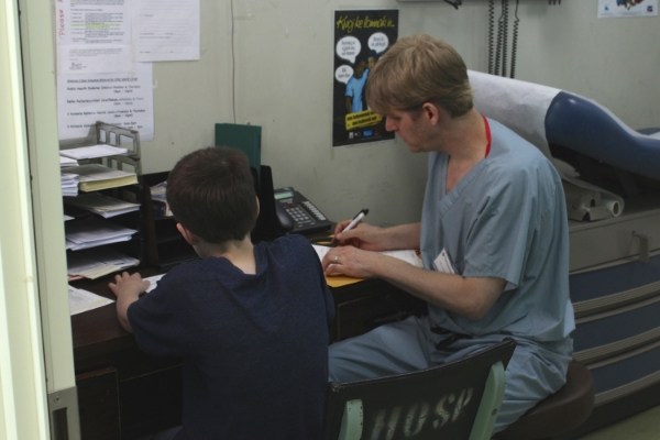 Joshua Anderson, left, assists his father Dr. John Anderson during orthopedic clinics. PC: Brian Hoffman.
