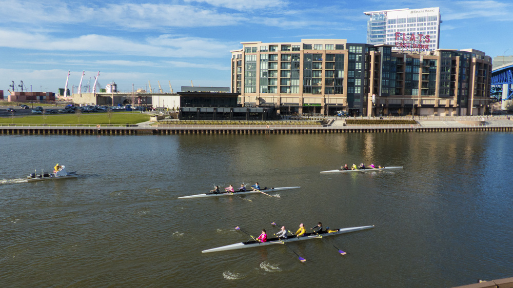 Rowers from St. Joseph Academy passing the Flats East Bank development