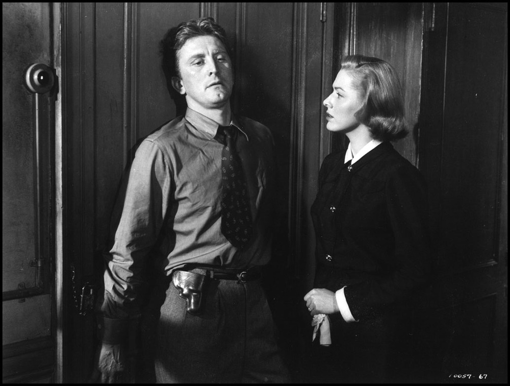 Kirk Douglas (left) and Eleanor Parker (right) depict a strained relationship between a troubled detective and his delicate wife in Detective Story (1951).