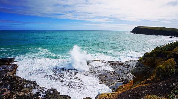 WAVES CRASH INTO THE COASTLINE DOWN AT CURIO BAY, NEW ZEALAND