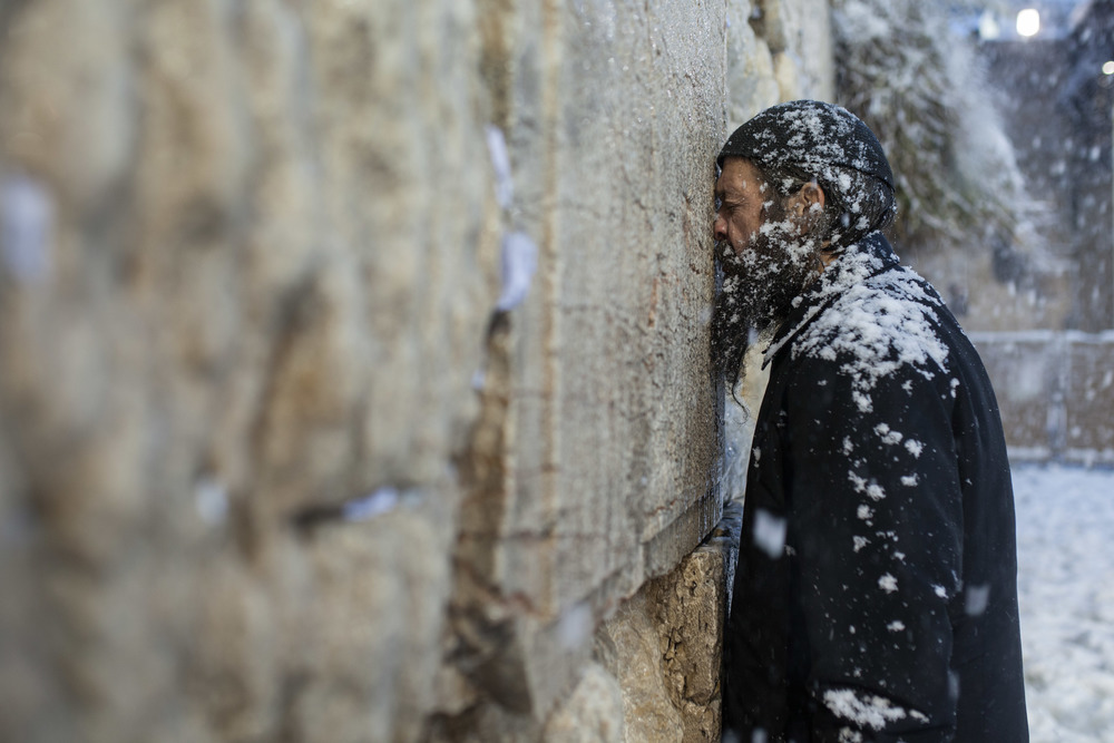 Ultra-Orthodox prays at the Western Wall in the snow Jerusalem 2013
