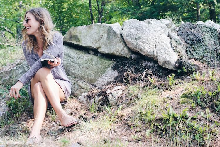 Jill Lansky seen wearing theJacquetta Henley Sleepwear Tunic in purple mix seated on a rock reading a book