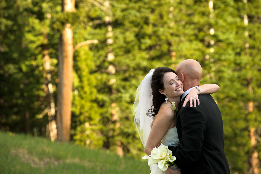 Bride hugging groom and smiling outside on keystone mountain