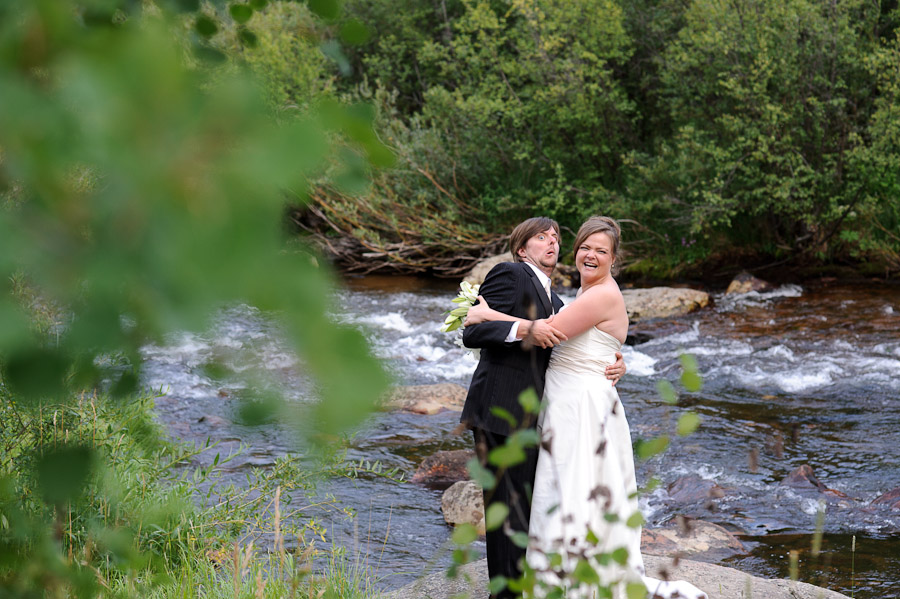 Bride throwing groom into water at Wild Basin Lodge in Roosevelt National Forest Colorado