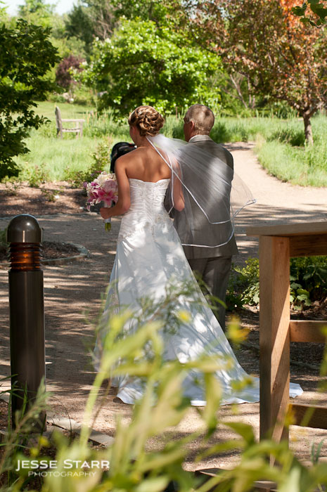 Bride and father of the bride share a moment before walking down the aisle at a wedding at the Hudson Gardens in Littleton Colorado