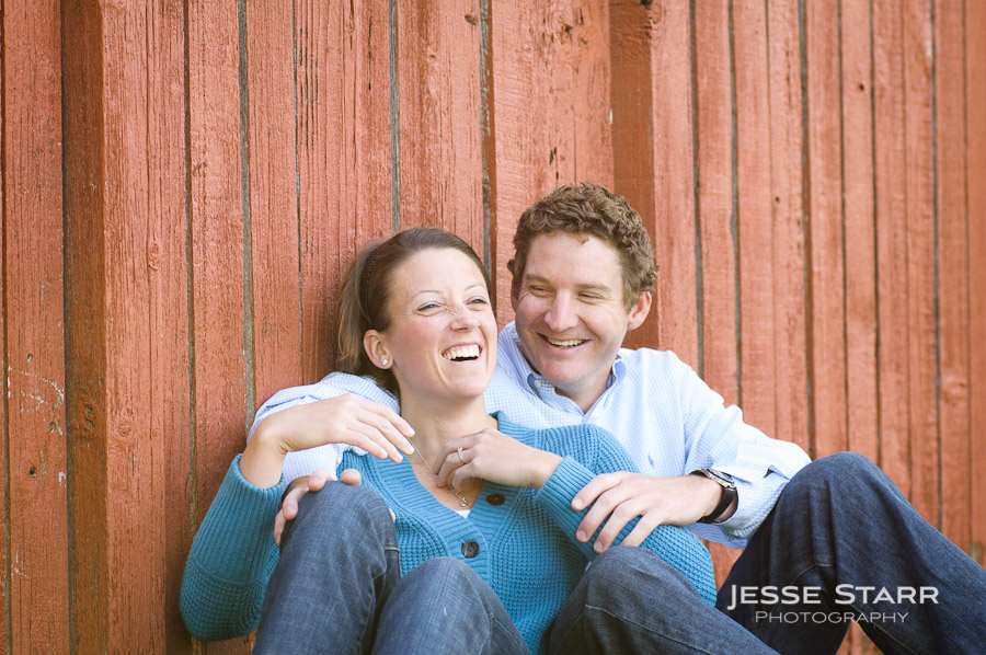 Couple laughing in front of red wood wall
