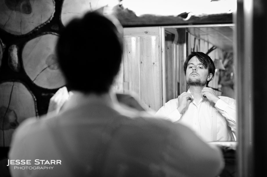 Groom adjusting collar in front of mirror