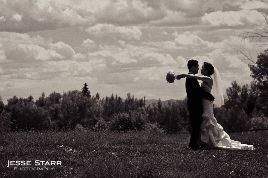 Bride and groom hug while standing in a field with mountains in the background.