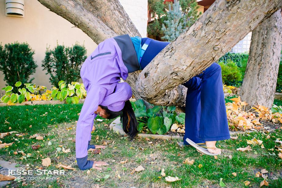 Girl doing backbend over tree branch in Lululemon Escapade Jacket