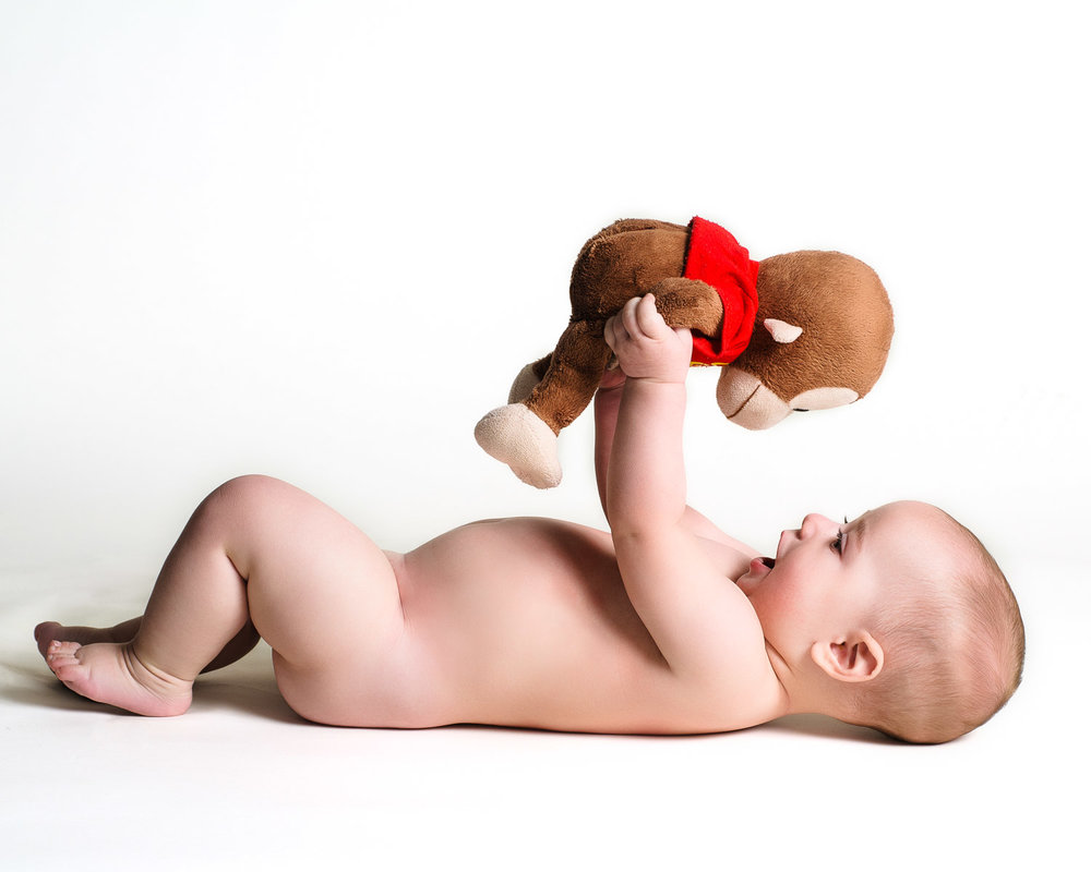 baby holds up curious George during baby photography session in