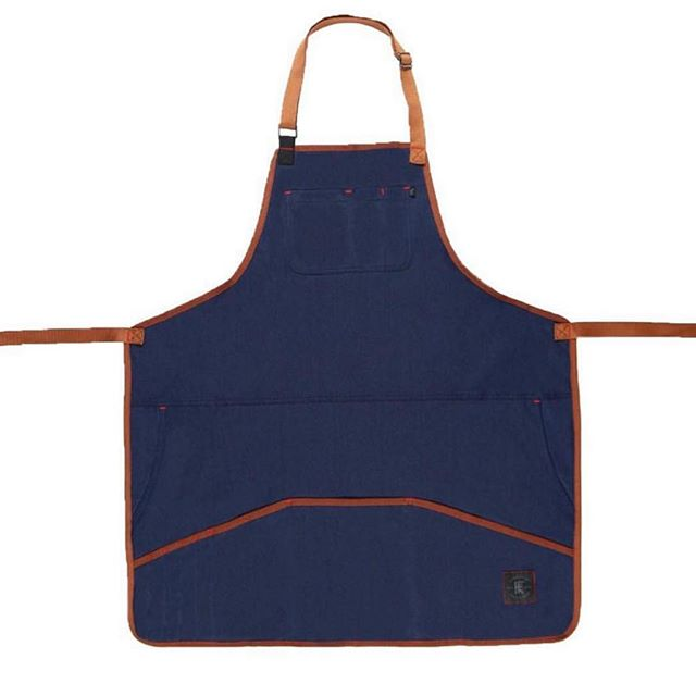 The Industry Apron, made from comfort stretch material (74% cotton, 24% poly, 2% spandex) with adjustable neck and waist straps. Waterproof! A large upper pocket with pen slots, jeans-style pockets on the sides, and large lower pockets provide all the room you'll need to store go-to gadgets during a hectic day on the job. Extra long straps! At only $50, it's one of our most affordable aprons. . . . #apron #knifeflag #knifeandflag #survivalunion #craftsman #barber #woodworking #maker #barberlife #mechanics #bartender #bar #tattooartist #craftsmanship #shoplocal