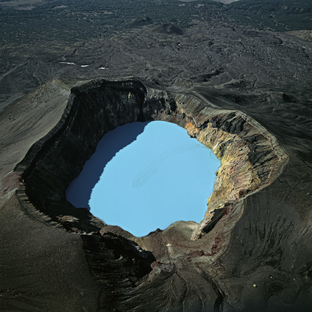 AERIAL IMAGE OF A VOLCANIC CRATER FILLED WITH A TURQUOISE-BLUE ACID LAKE PHOTOGRAPHED BY BERNHARD EDMAIER IN SOME/THINGS MAGAZINE CHAPTER005