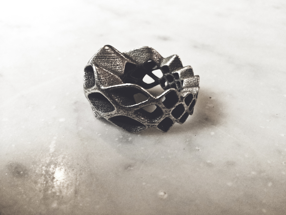 mesh ring, 3D printed steel ring, photography ldvc ludovico lombardi  the mesh is formed and informed by the finger to create constant and gradient variations of the mesh looping around the fingers. the mesh quads are bot the structure and the ornament of the ring in an integrated design solution.