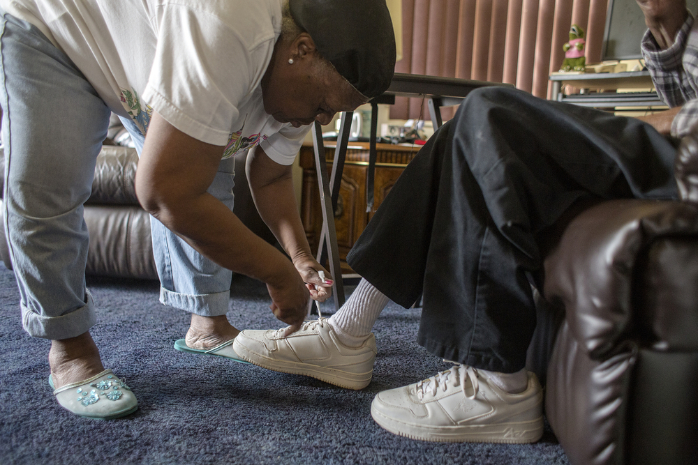 Beatrice Ford ties her husband's shoes after getting him out of bed in their east-side Detroit home, June 10, 2014. Hugh Ford calls to his wife from bed around 10 a.m. every morning to begin their daily routine. She washes, changes and dresses him, walks him to the chair he'll sit in all day, hands him a cup of coffee and a pack of mini donuts, and then cleans his mattress.