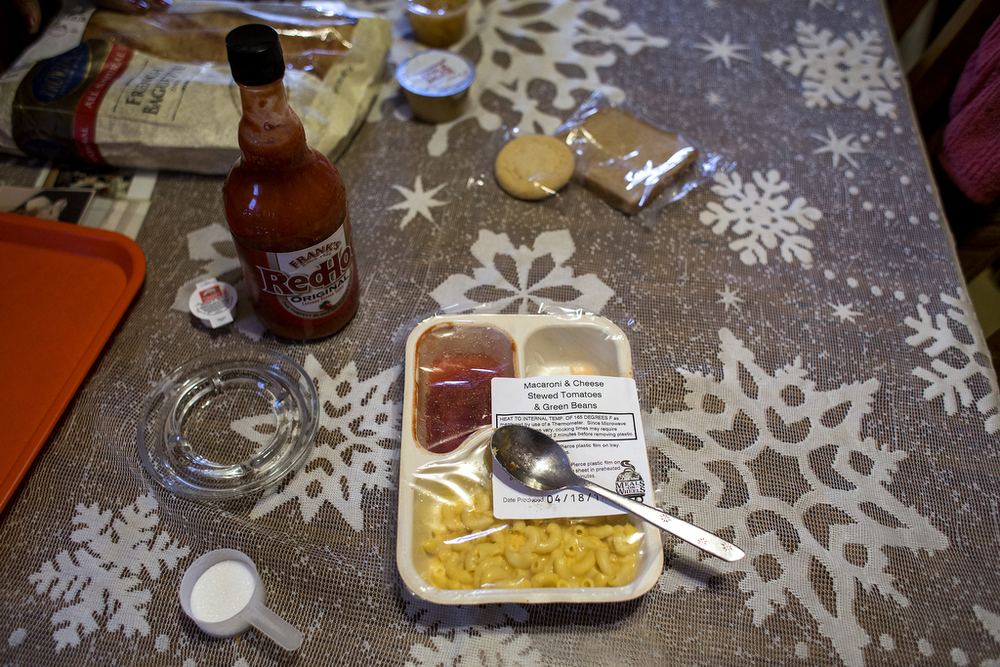 "Hugh Ford's Detroit Meals on Wheels dinner of macaroni and cheese, green beans and stewed tomatoes sits in its plastic container before his wife ""doctors it up"" with hot sauce and sugar. Ford is one of 2,250 older adults Meals on Wheels serves with either daily hot meals or a box of five frozen meals every week. Another 250 seniors are on a waitlist for the service. Beatrice Ford said the food is good, for the most part, but her husband, a picky eater, needs some extra flavor."