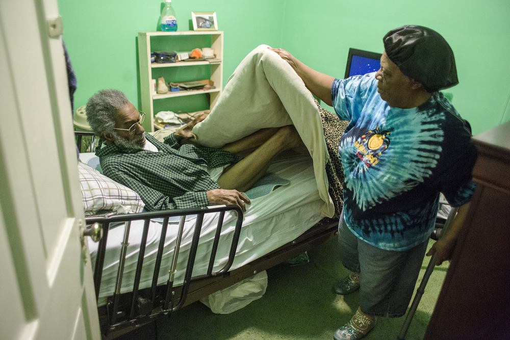Beatrice Ford pulls blankets over her husband Hugh Ford as she puts him to bed, Friday, May 2, 2014. Beatrice Ford spends her entire day caring for her husband, who has dementia and is blind in one eye. Despite the increasing difficulty and cost of taking care of him at home, Ford said she would never put him in a nursing home; she could never live with herself if she did that.