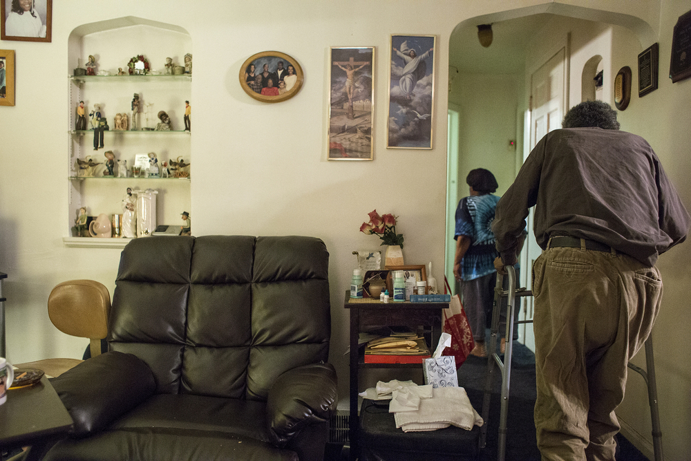 Hugh Ford follows his wife, Beatrice Ford, to his bedroom in the back of their east-side Detroit home late Friday, May 2, 2014. After Beatrice Ford puts him to bed, she cleans up the house, double checks the locks, says a prayer for her husband and their leaky roof, turns off the light and goes to sleep in her separate bedroom across the hall.