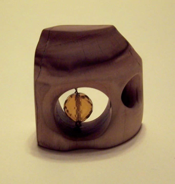 apple-wood-sculpture-with-faceted-amber-bead-in-the-center-of-a-round-hole.jpg