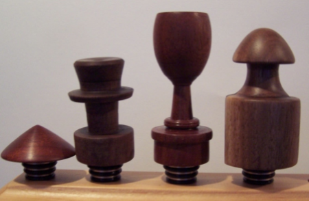 Bottle Stoppers are one of my specialties.  Turned wood tops with surgical Stainless Steel and food quality silicone rubber seal bases tapered to fit most bottles.  The stoppers can be used with any liquid and it will not rect.   I enjoy making shapes like tiny shot glasses and little hats.
