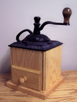 Handmade oak coffee grinder with cast iron top.