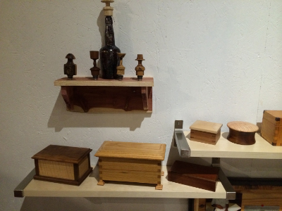 Top cedar shelf showing bottle stoppers George turns.  Next shelf on right holds square cherry box with key joints on the corners and maple lid, next is turned walnut box with curly maple lid, and next is oak with box joint corners.  Lower shelf holds a flamed maple box with walnut top and corners, ash box with box corners, distinctive square pedestal  feet and hinged lid.  next is mahogany box with lift off lid.