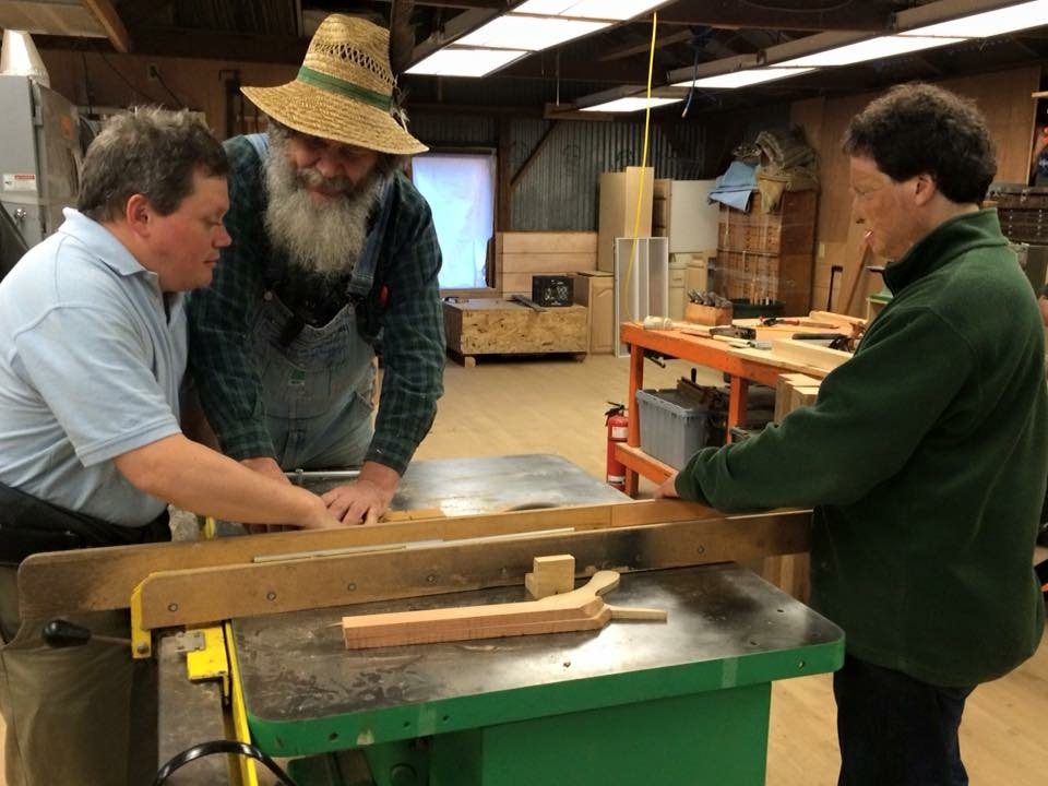 George Wurtzel showing two students how to use a table saw