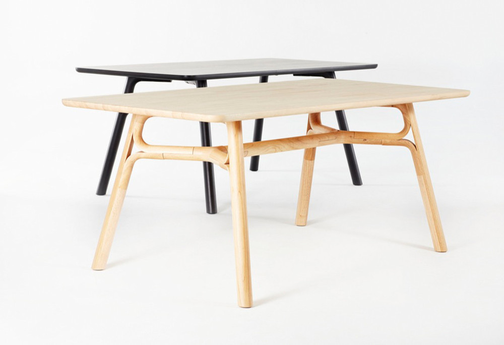 Justin Hutchinson's 'Flow' table in natural and black finishes. The design uses a number of interlocking curved pieces to achieve it's wishbone-like structure. Hutchinson also designed a coffee table and side table using this leg design.