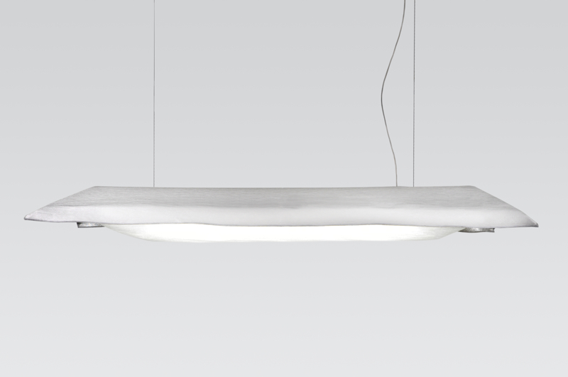 The light utilises a double weave jacquard 'pocket' developed by Pot with the Tilburg Textile Museum. The top surface is white while the internal face is reflective silver to direct the light downwards. The thin white diffuser is the third layer.