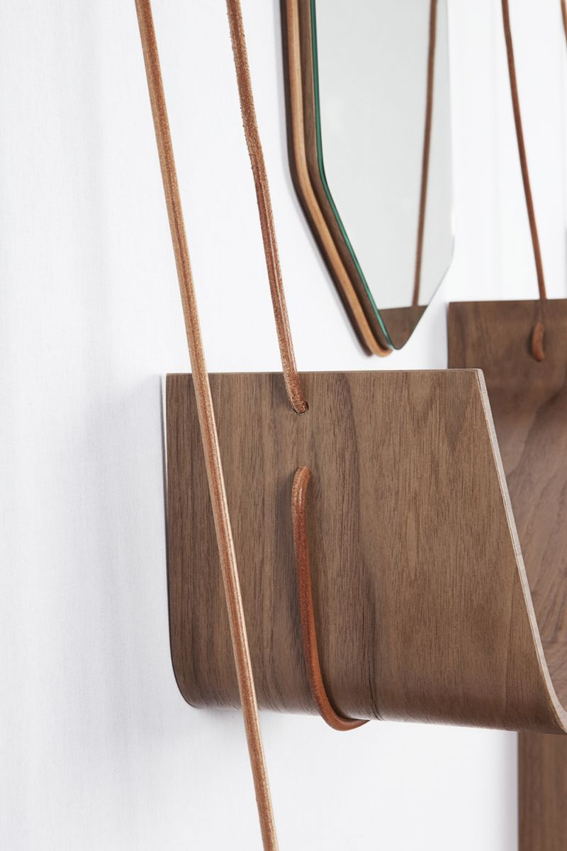 A close up of the 'Vola' hanging shelving system with its heavy leather cord and moulded plywood shelves.