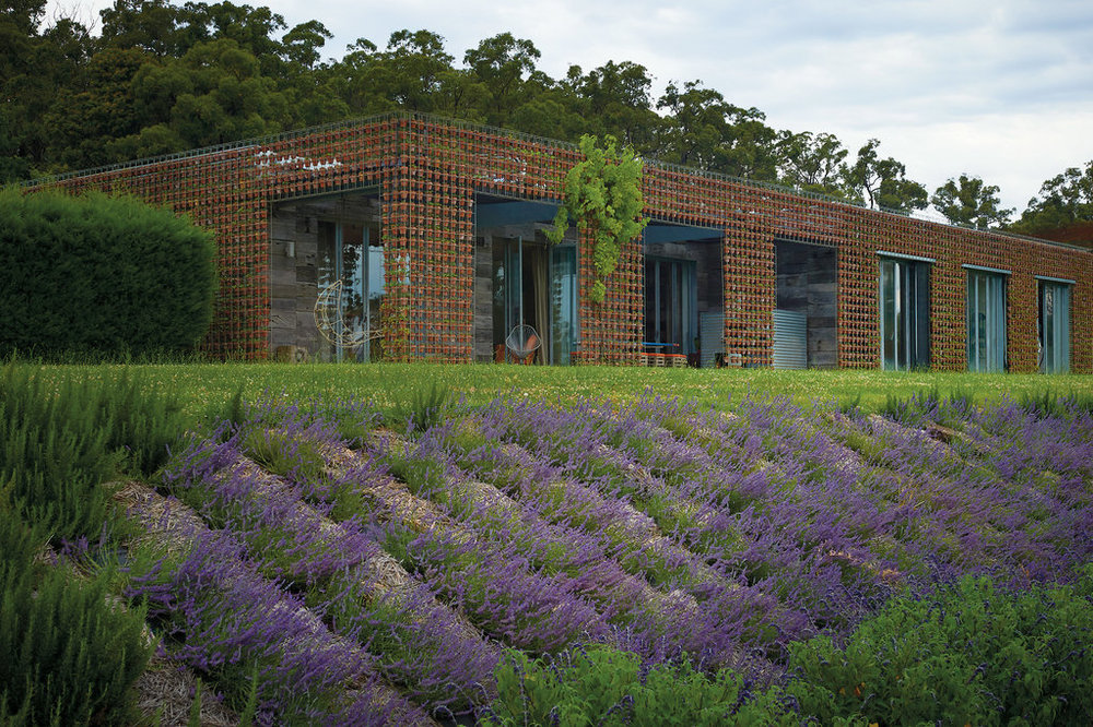 The home of Australian landscape designer Joost Bakker in Monbulk Victoria. The walls are an open rebar grid filled with terracotta pots filled with 11,000 strawberry plants. Photo: Earl Carter.