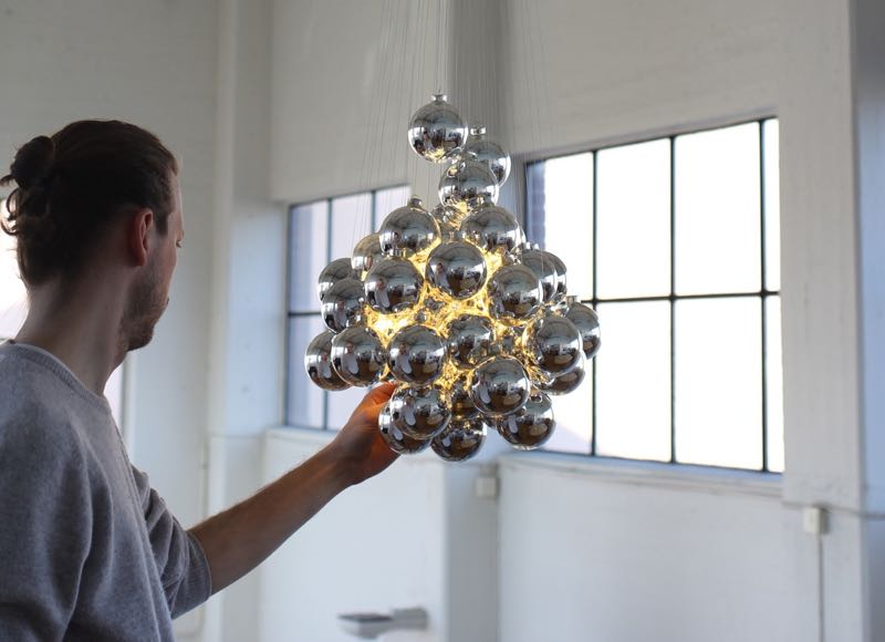 Daniel Rybakken with a prototype of his 'Stochastic' pendant light for Luceplan.