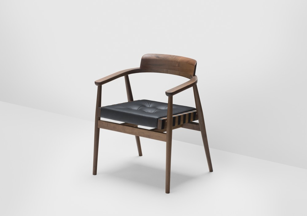 The 'Leather' chair in walnut with solid timber back. Another version uses padded leather on the backrest.