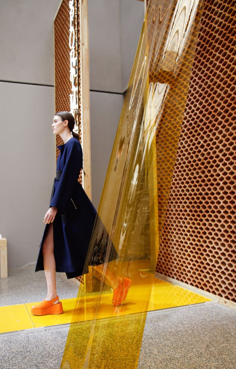 The entrance of the Sportmax Spring / Summer 2016 show, revealing the terracotta wall, acrylic runway and PVC dividers. Shiny yellow meets earthy clay - an expression of Italian summers of the 60's & 70's.
