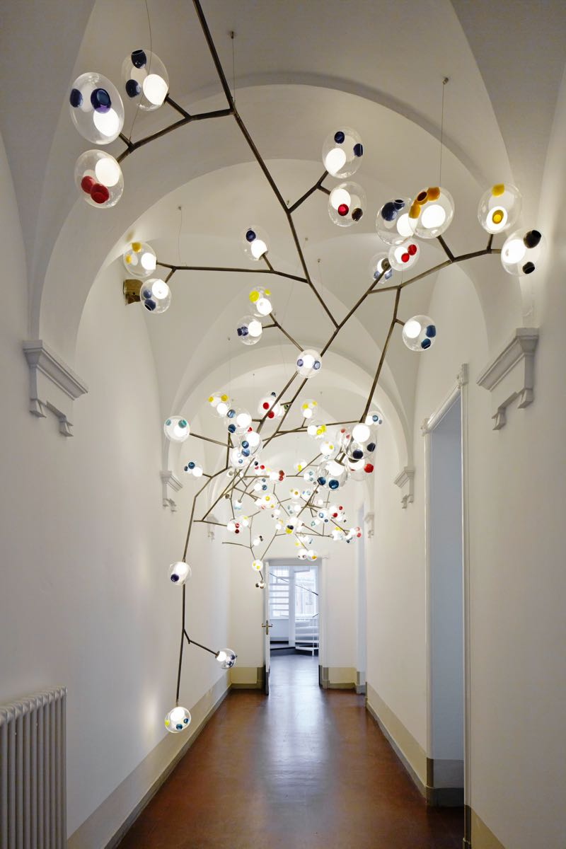 Bocci '28' lights mounted on armatures down a hallway of the brand's Berlin showroom.
