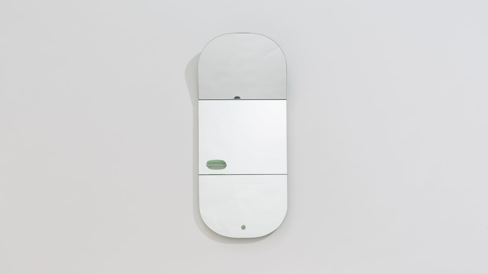 One of the the original mirrors designed for the 1+1+1 project by Finnish studio Aalto Aalto. It includes a small glass shelf and angled top section.