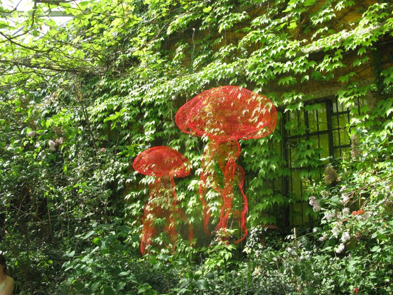 The lush green courtyard of Rossana Orlandi wit shimmering red squids by Benedetta Mori-Ubaldini
