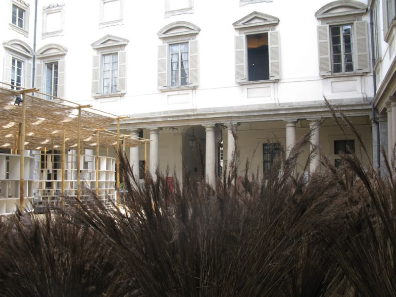 The courtyard of Palazzo Litta was transformed by grasses that softened the architectural elements and reflected the materials used in the structure (to the left of the image) that provided outdoor space for a series of designer talks.