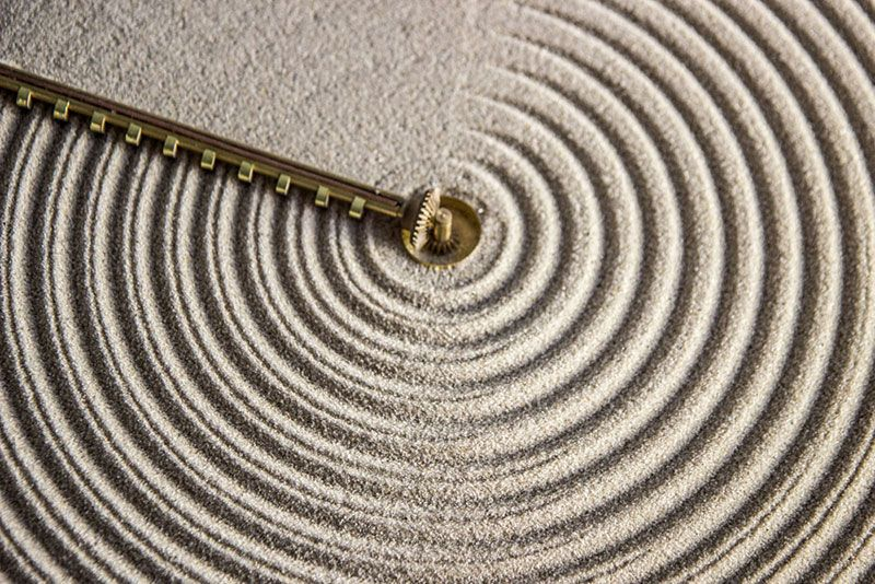 The 'Ripples of Time' clock by Studio Ayaskan - an earlier design that raked and then flattened sand leaving a visual impression of time in front and behind the sweeping arm.