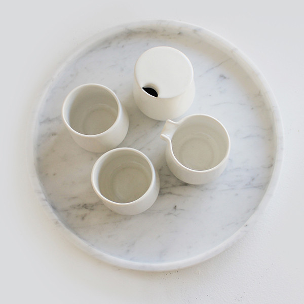 The new 'Round tray' in marble with porcelain vessels from the older 'Emily Tea Set', both by Evie Group.