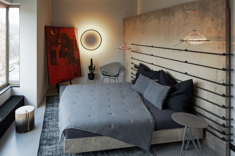 The main bedroom of the loft features full width bed head feature wall with a creative use of concrete reinforcing steel (rebar).