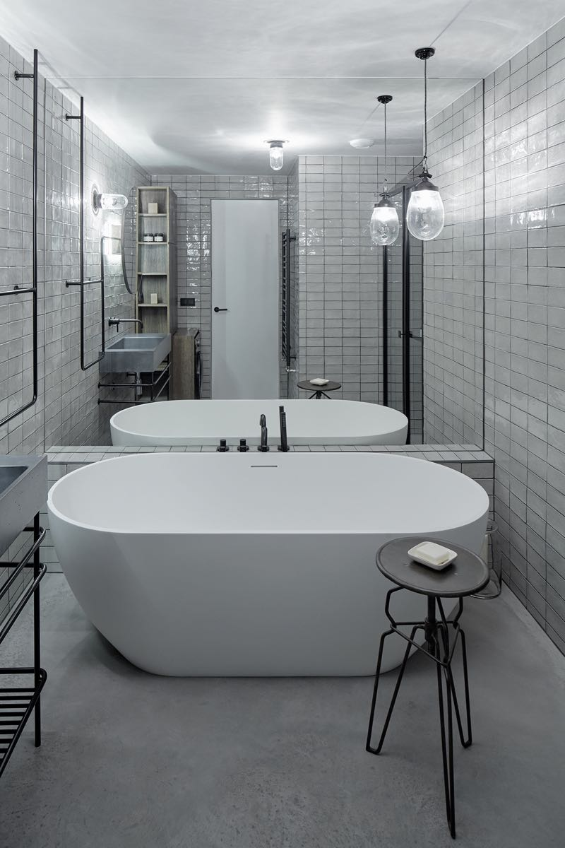 The bathroom is tiled from floor to ceiling ain handmade white tiles from Altair. The bath is called 'Bilbao' and is from Riho.