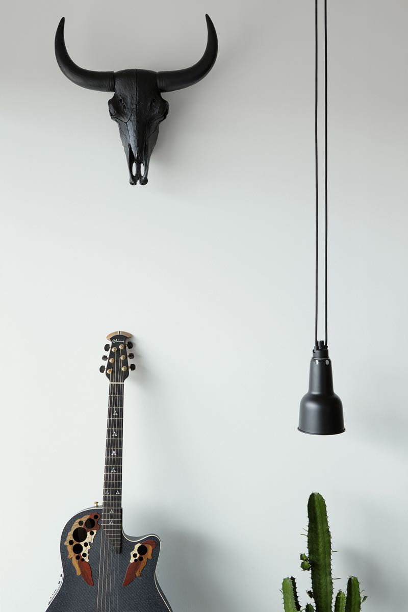 A black cow skull and guitar are some of the few hints that the owner of the apartment is male.