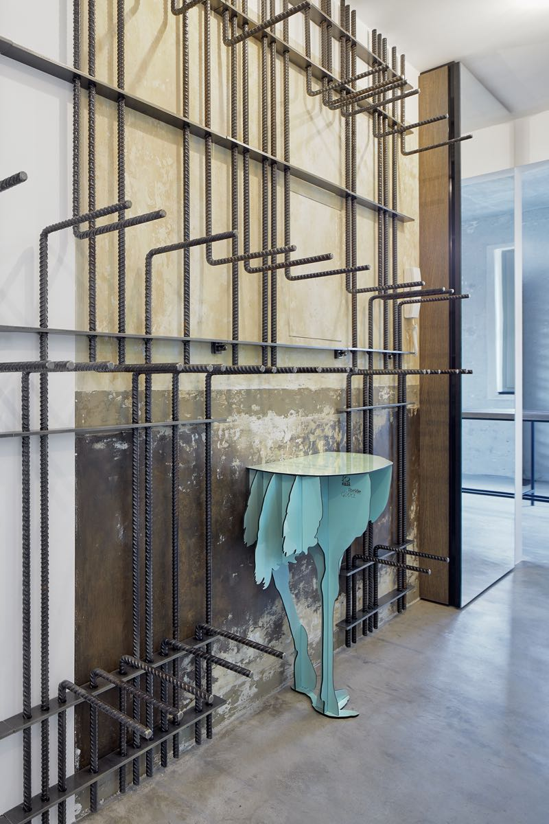 The entrance wall with its rebar structure for hats and coats. The console table is the 'Diva' from French company Ibride.