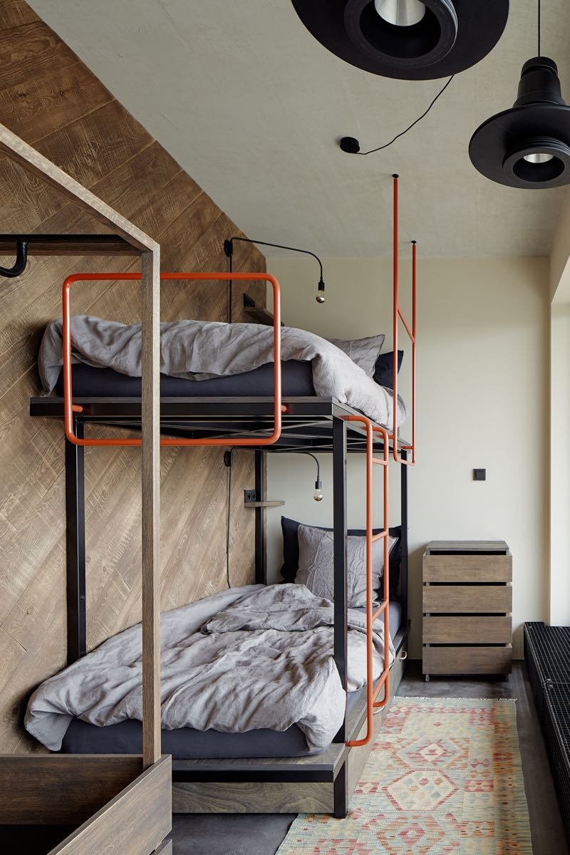 A custom made bunk bed continues the pipe theme that exists in the bathroom and kitchen. This time around it is given a bright orange colour.  The pendants are from Diesel.