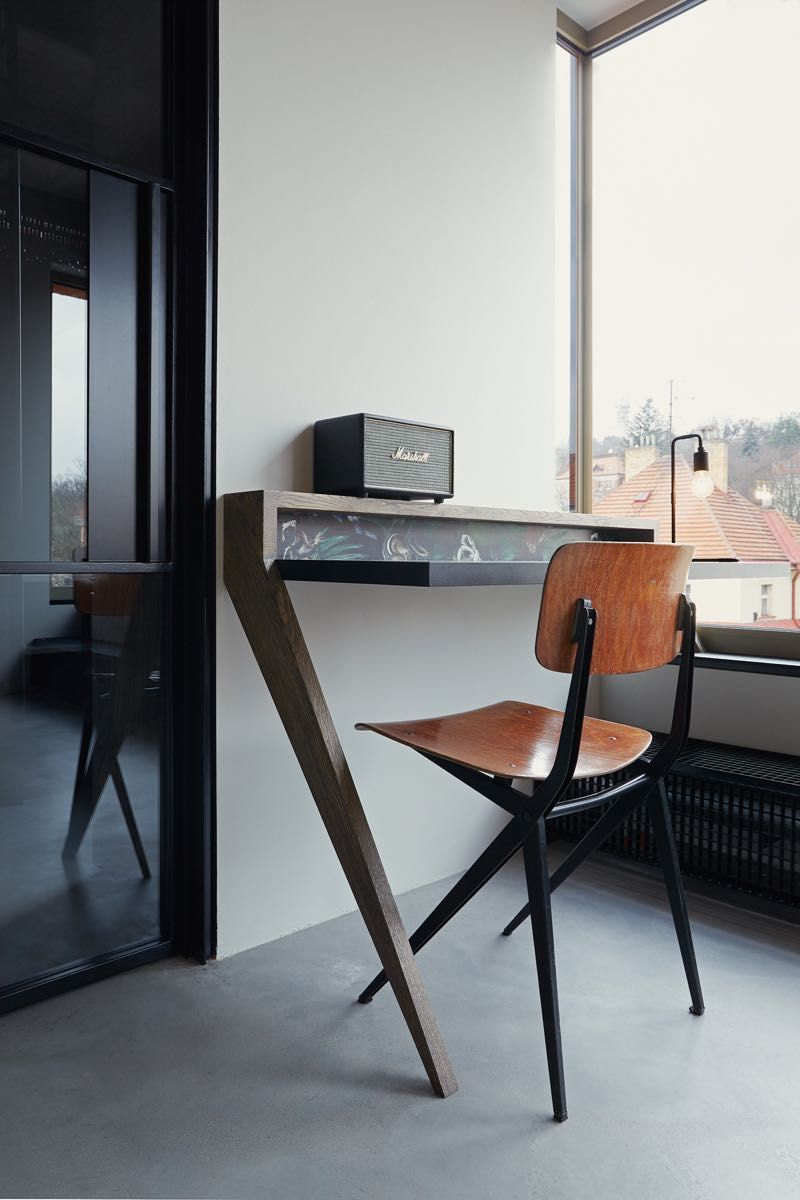 A vintage Dutch Marko chair sits opposite a leaning writing desk.