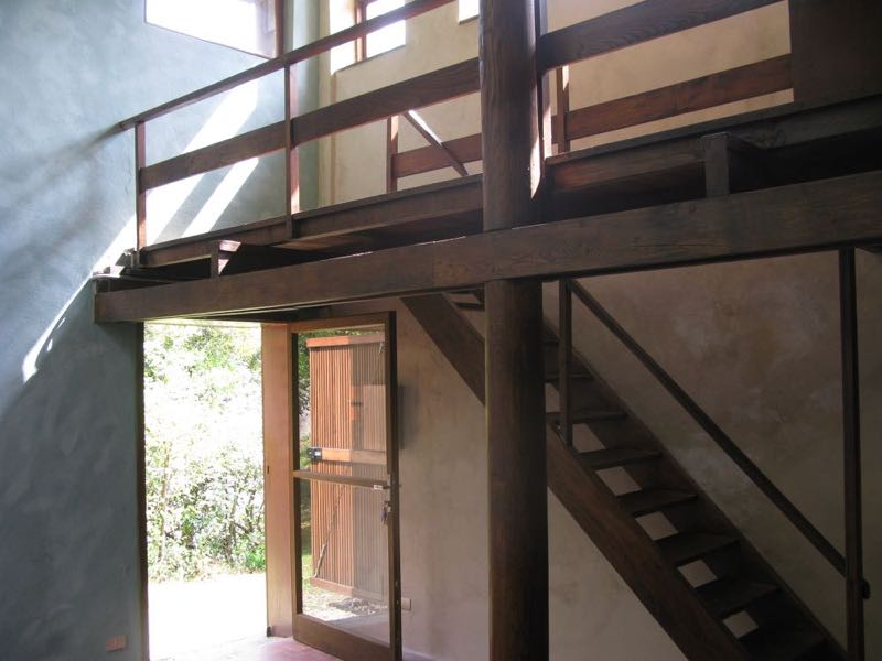 The interior of House B with its mottled plaster wall (left) and simple chestnut stair & mezzanine.